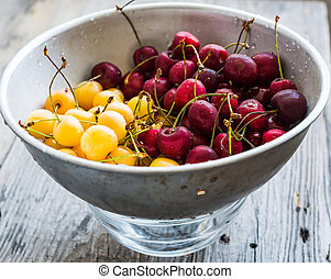 fresh sweet cherries red and yellow in a metal colander
