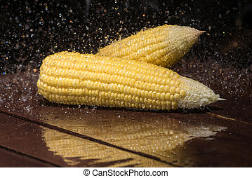Fresh sweet corn on wooden table.