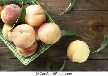 Fresh sweet peaches on the wooden table