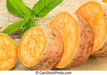 Fresh sweet potato sliced closeup , on wooden background