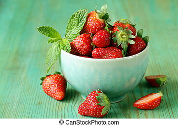 fresh sweet ripe strawberries in a bowl on a wooden table