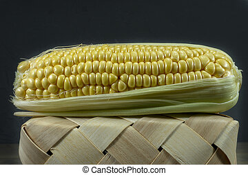 Fresh sweetcorn cob on a tipped wicker basket