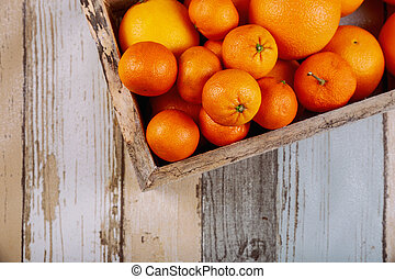 Fresh tangerines in old box with on wooden background.