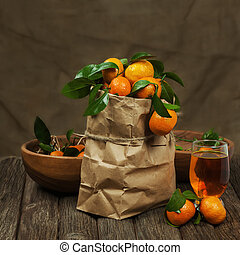 Fresh tangerines in recycle paper bag and glass of juice on wooden table. Closeup.