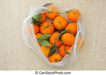 Fresh tangerines with leaves in a plastic bag