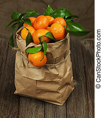 Fresh tangerines with leaves in recycle paper bag on wooden table.