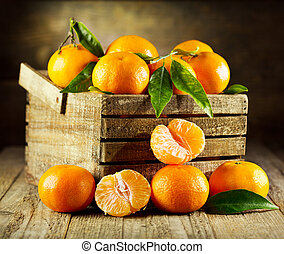 fresh tangerines with leaves in wooden box