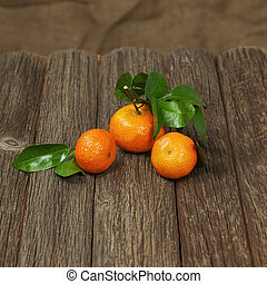 Fresh tangerines with leaves on a wooden table.