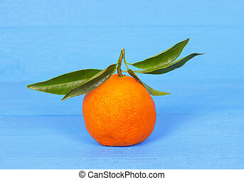Fresh tangerines with leaves. On wooden background.