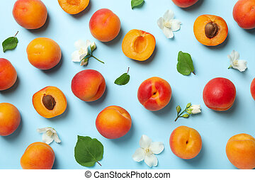 Fresh tasty apricots on blue background, top view