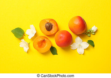 Fresh tasty apricots on yellow background, top view