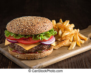 fresh tasty burger and potatoes on wooden board