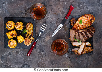 Fresh three types of grilled steak (chicken, pork, beef) on slate plate with herbs, tomato, juice, corn and grilled potatoes