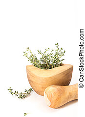 Fresh thyme in  wooden mortar with pestle, on withe background.