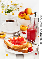 Fresh toasts with jelly, cup of coffee and fruits for breakfast