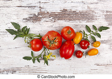 Fresh tomato fruits on wooden background from above.