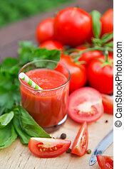 Fresh tomato juice on wooden background