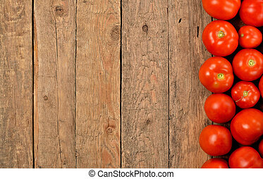 Fresh tomato on wooden background. Top view with copyspace.