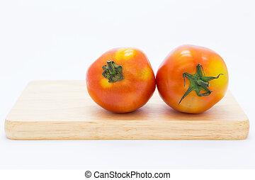 Fresh tomato on wooden board