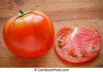 fresh tomato on wooden cutting board