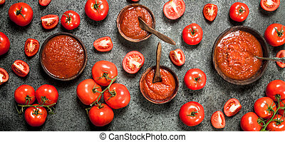 Fresh tomato sauce with spices. On rustic background.