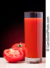 Fresh tomatoes and a glass full of tomato juice.