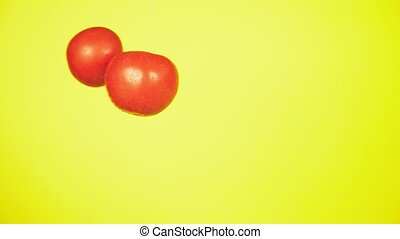 Fresh tomatoes fall with drops of water. The concept of nutrition. Isolate on a yellow background, slow motion