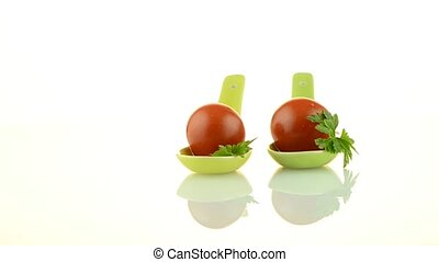 Fresh tomatoes and parsley leaves  on ceramic spoons.