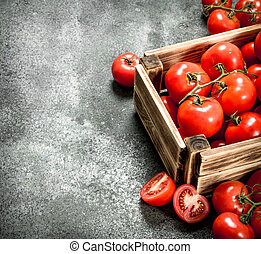 Fresh tomatoes in a wooden box.