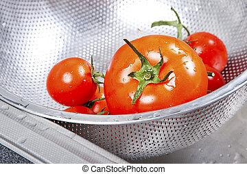 Fresh tomatoes in colander splashing in water