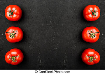 Fresh tomatoes on black background. Autumn vegetable concept, close-up view
