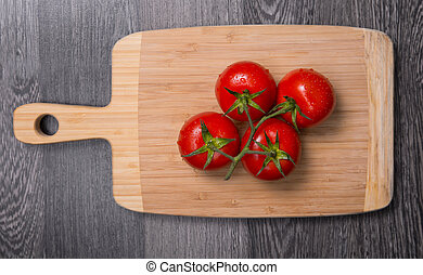 Fresh tomatoes on chopping board