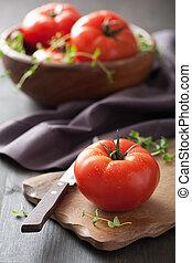 fresh tomatoes on cutting board