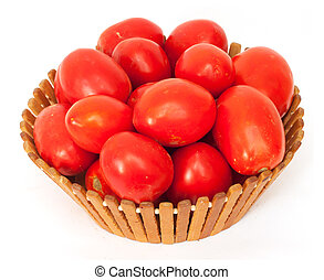 fresh tomatoes on green branch in wicker basket isolated on white background