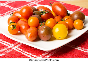 Fresh tomatoes on white plate