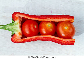 Fresh tomatoes, peppers arranged on a board