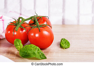 Fresh tomatoes with basil leaves in the wood background