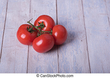 fresh tomatoes with green on a wooden table