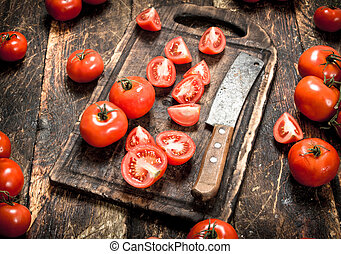 Fresh tomatoes with old hatchet on a chopping Board.