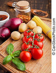 Fresh tomatoes with vegetables and basil on wooden board