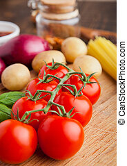 Fresh tomatoes with vegetables on wooden board