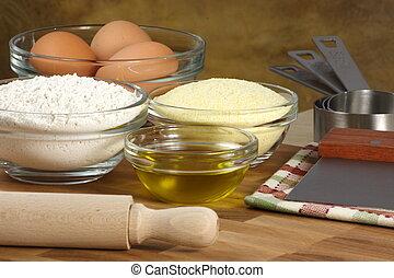 fresh raw tortellini ingredients on kitchen wood station with utensils