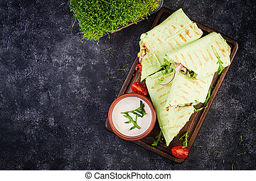 Fresh tortilla wraps with chicken and fresh vegetables on wooden board. Chicken burrito. Healthy food concept. Mexican cuisine. Top view, overhead