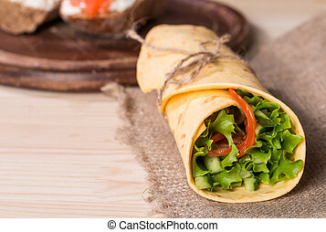 fresh tortilla wraps with vegetables on wooden background