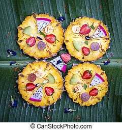 Fresh tropical fruit pizza with pineapple, strawberry, kiwi, grapes, banana and dragon fruit, Thailand