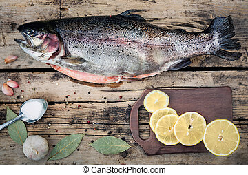 Fresh trout fish with spices on wooden background