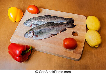 Fresh trouts on wooden cutting board