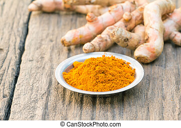 Fresh turmeric root, and turmeric powder on wood background- shallow depth of field