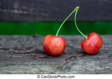Fresh two sweet cherries on a wooden bench background. fresh ripe cherries. 2 cherries in the open air on the background