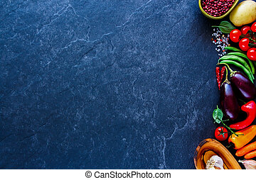 BIO food. Food background. Fresh raw unprocessed vegetables and grains over stone kitchen countertop, top view, copy space. Clean, healthy eating, vegan, detox, dieting food concept